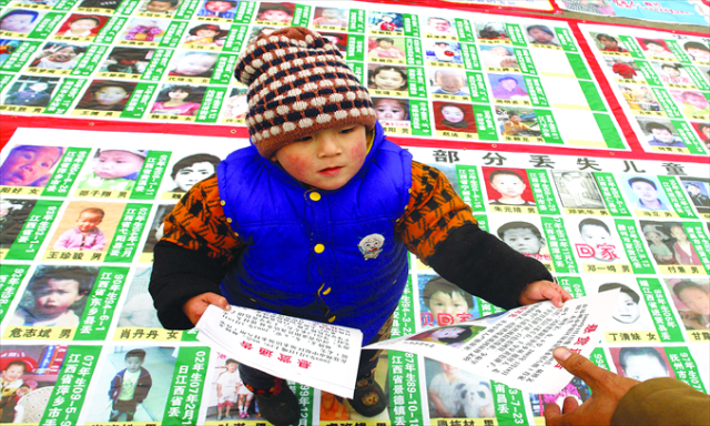 Chinese child hands out leaflets about his missing brother