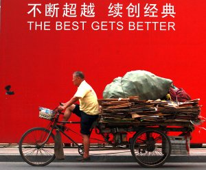 A poor Chinese man hauls his day's 'catch' of recyclable trash in Beijing